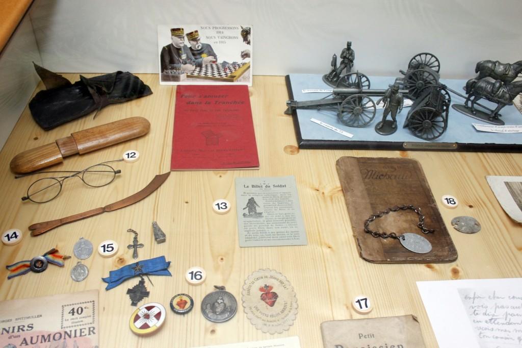 Les petits objets numérotés 15 et 16 (médailles de la vierge, croix, sacré cœur) renseignent sur les croyances religieuses. Ces objets de protection étaient souvent expédiés aux poilus par leur famille.