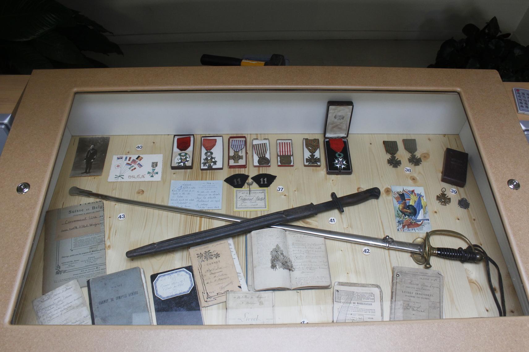 Des médailles, carnets, épée.
