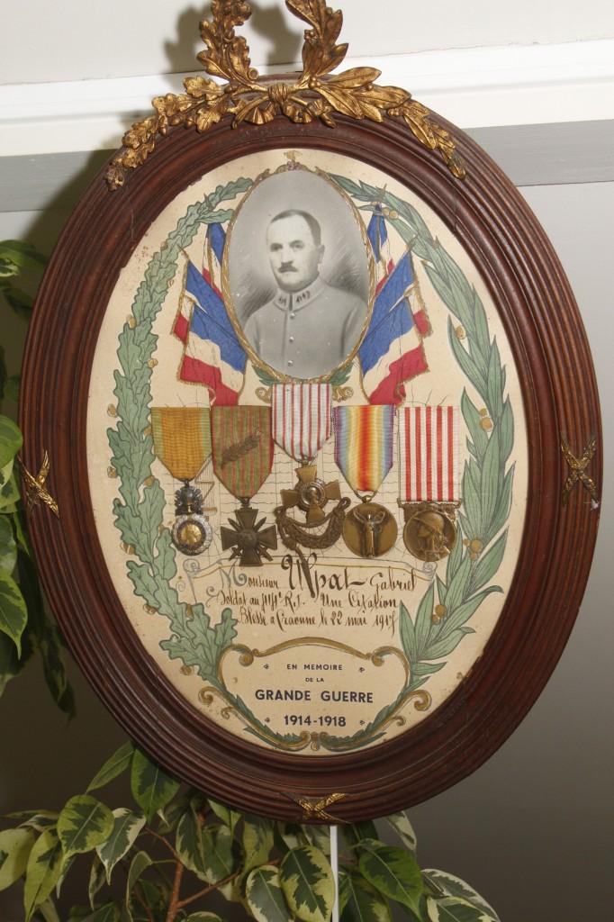 Médailler de Gabriel Ulpat prêté par la famille. Forme ovale, cadre en bois et bronze. En haut sa photographie entourée de six drapeaux tricolores. Les lauriers de la Victoire offrent un cadre aux cinq médailles (croix de guerre avec palme, médaille militaire…).